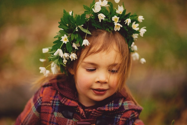 The pretty girl has a wreath of snowdrops