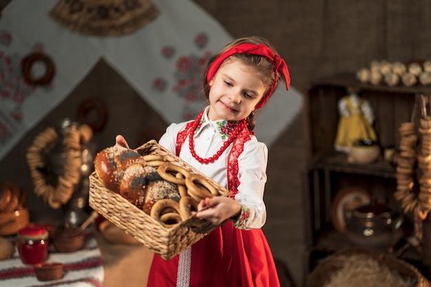 Maslenitsaを祝う伝統的な家でベーグルと他のベーキングのバスケットを保持しているきれいな女の子