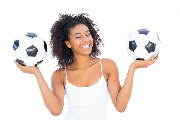 Pretty girl holding footballs and smiling at camera