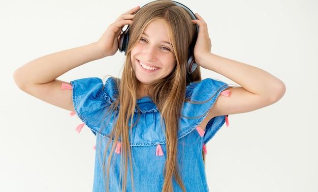 白で隔離される彼女の頭にヘッドフォンを持っているかわいい女の子