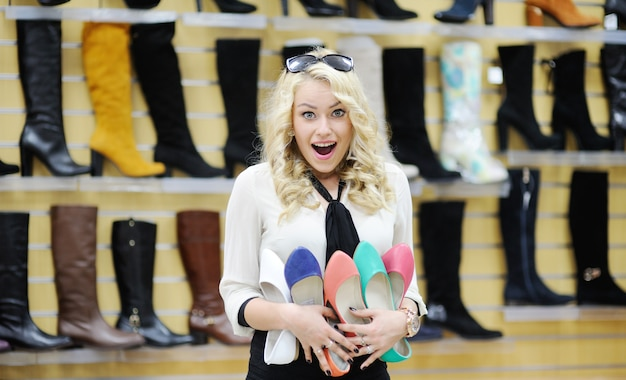 Pretty girl holding a lot of colorful shoes. shopaholic woman chooses shoes
