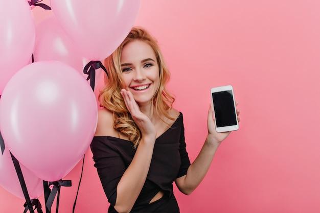 Ragazza graziosa che tiene nuovo telefono e sorridere. la donna bionda alla moda ottiene uno smartphone come regalo di compleanno.