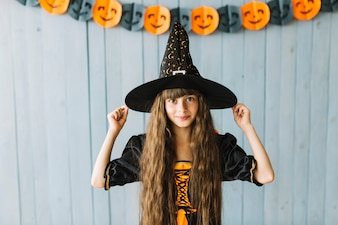 Pretty girl holding on witch hat and smiling at Halloween party