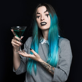 Pretty girl holding wineglass with green liquid