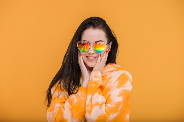 Pretty girl in hoody posing on bright orange background