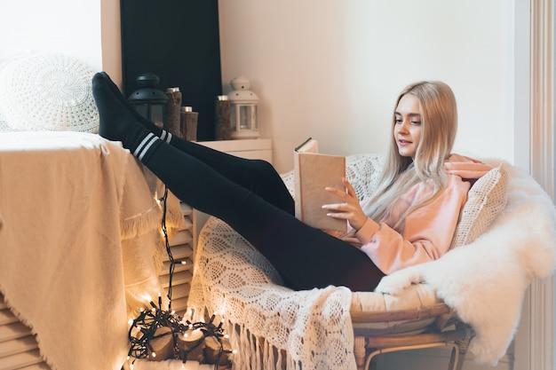 예쁜 여자가 창문 근처의 편안한 둥근 안락 의자에 누워있는 동안 책의 놀라운 세계를 상상