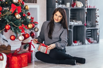 Pretty girl in a grey sweater poses before a Christmas tree with red toys