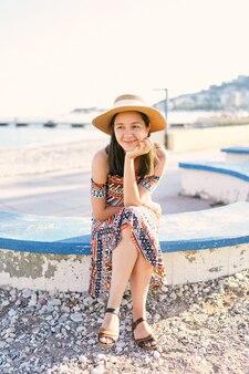 모자와 드레스를 입은 예쁜 여자가 자갈 해변의 벤치에 앉아 있다