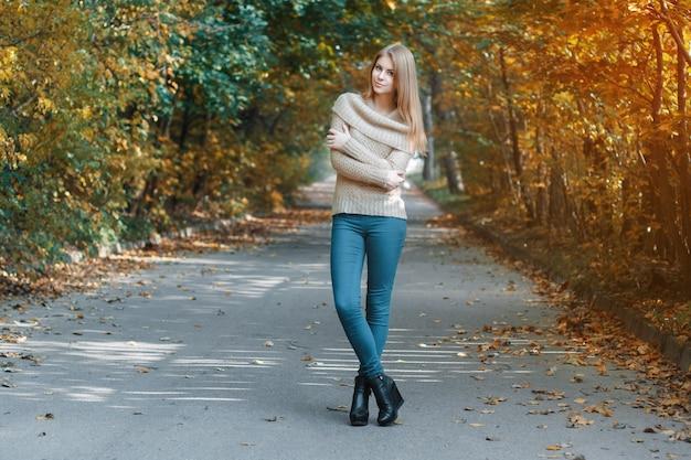 秋の公園に立っているプルオーバーのかわいい女の子