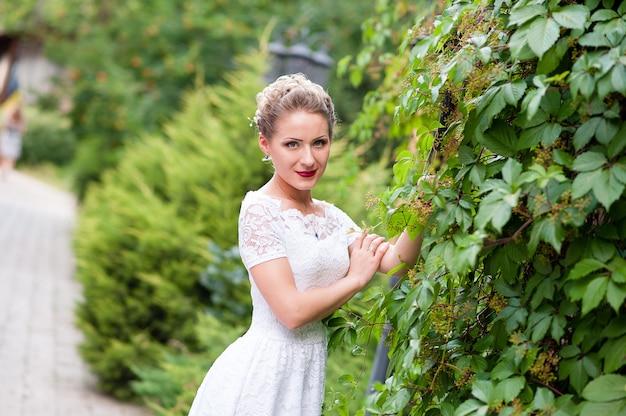 Красивая девушка в белом платье на открытом воздухе.