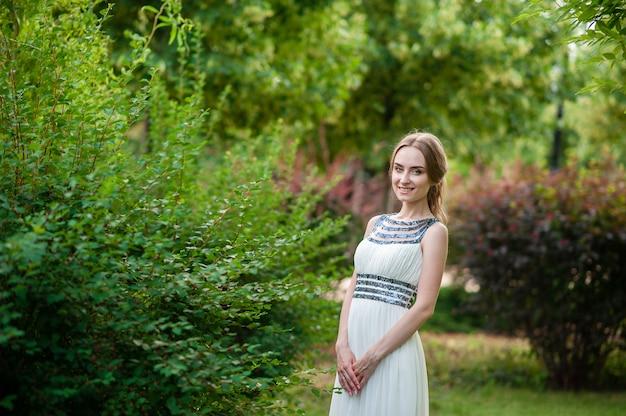 Красивая девушка в белом платье, прогулки в парке.
