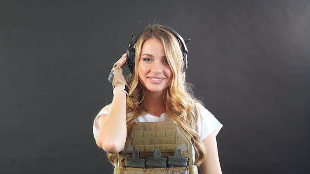 エアソフトの制服とヘッドフォンでかわいい女の子は、バックグラウンドで煙と暗い背景に対してポーズします。