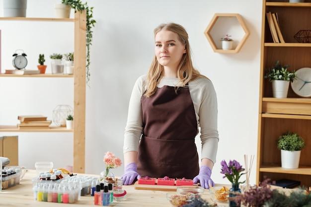 Красивая девушка в фартуке и перчатках смотрит на вас, стоя у стола во время мастер-класса по мыловарению
