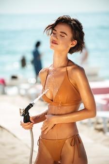 Красивая девушка в бикини с помощью шланга на пляже. портрет дамы в бежевом купальнике, смывающей пляжный песок со своего тела на пляже. молодая девушка мечтательно закрыла глаза, наливая воду из шланга на пляже