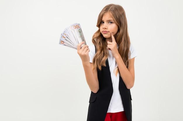 Красивая девушка в черном и красном костюме держит деньги и улыбки на белом фоне