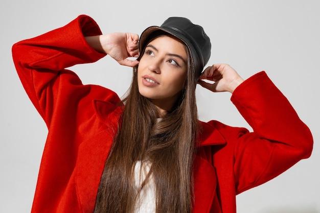 Красивая девушка в черной шляпе и красном пальто подняла руки и держала кепку в студии на белой стене