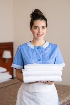 ホテルでの作業中に新鮮な白いタオルのスタックを押しながらあなたを見て青い制服と白いエプロンでかわいい女の子