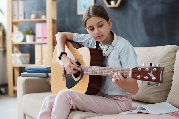 소파에 앉아 자기 검역 중 집에서 수업을 듣는 동안 기타를 연주하기 위해 공부하는 casualwear에 예쁜 여자