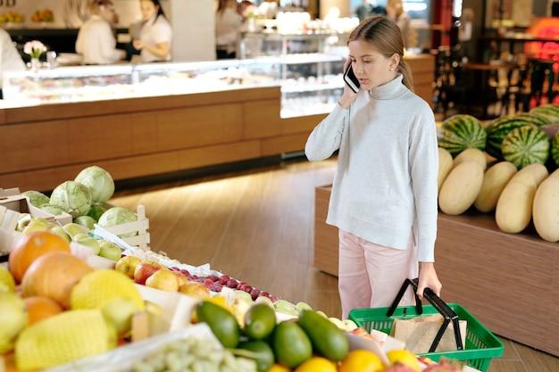 Красивая девушка в повседневной одежде разговаривает с мамой по мобильному телефону