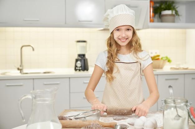 Милая девушка в шляпе шеф-повара варя печенья на кухне.