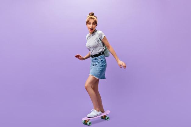 デニムスカートの可愛い女の子がロングボードに乗る。孤立した背景にポーズをとる灰色の流行のシャツと白いスニーカーの素晴らしいクールな若い女性。