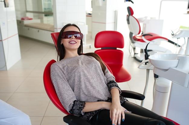Красивая девушка в очках в стоматологии