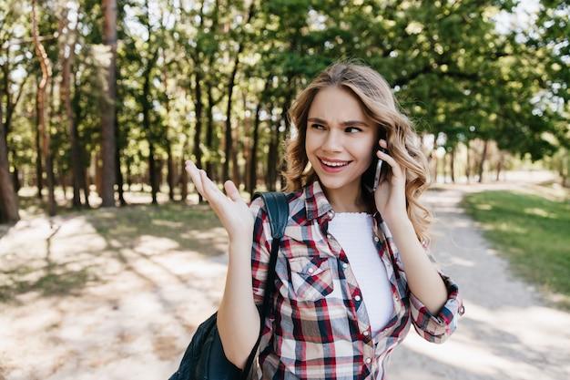 공원에서 산책하는 동안 좋은 분위기의 전화 친구 예쁜 여자. 배낭과 전화와 함께 포즈를 취하는 즐거운 곱슬 여자의 야외 촬영.