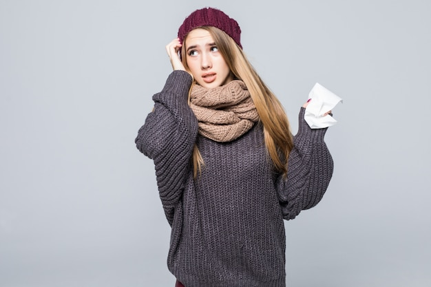 Красивая девушка в сером свитере остыла от гриппа на сером