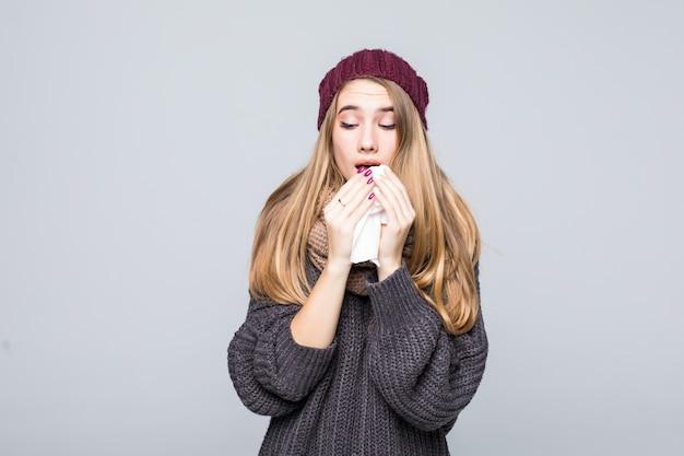 Красивая девушка в сером свитере остыла от гриппа, чихнув, головная боль на сером