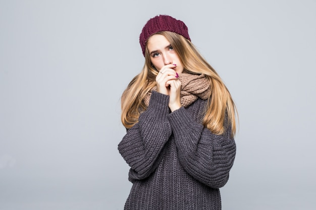 Красивая девушка в сером свитере замерзла, пытаясь согреться на сером