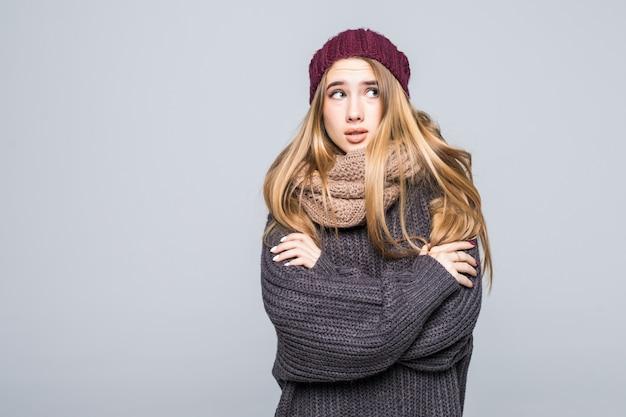 灰色のセーターを着たかわいい女の子は冷たい灰色でウォームアップしようとしています。