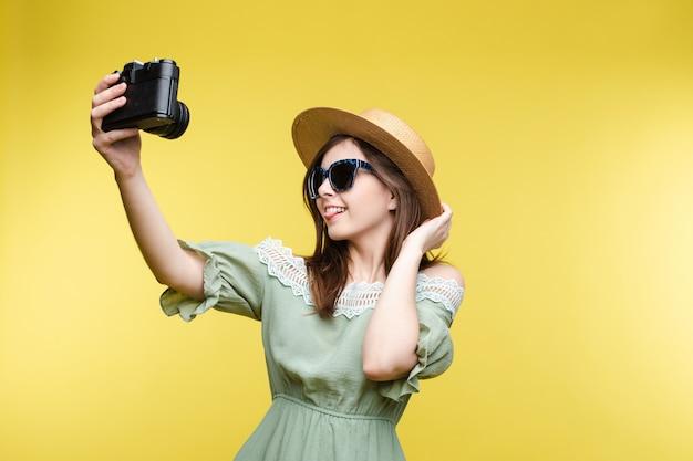Красивая девушка в шляпе и летнее платье принимая selfie на камеру.
