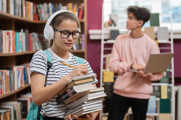 Красивая девушка в наушниках и очках держит стопку книг, стоя у книжной полки и составляет список литературы