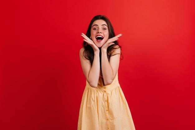 기분이 좋은 예쁜 소녀가 얼굴을 만지고 감정적으로 포즈를 취합니다. 미소로 체크 무늬 드레스에 여자입니다.