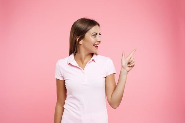 ピンクの壁でポーズいいスポーツ服でかわいい女の子