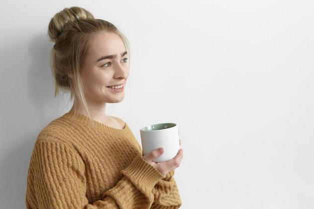 寒い秋の日にウォーミングアップ、コーヒーを飲み、大きなマグカップを持って、嬉しそうに笑っている特大のセーターを着たかわいい女の子。お茶と一緒に家でリラックスした髪の結び目を持つ魅力的な若い女性