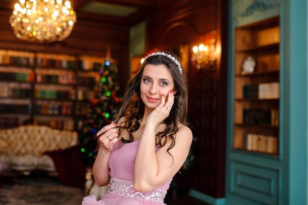 クリスマスツリーの近くのピンクのドレスを着たかわいい女の子。