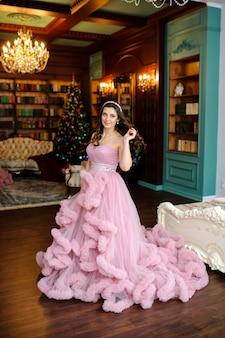 Красивая девушка в розовом платье возле елки.