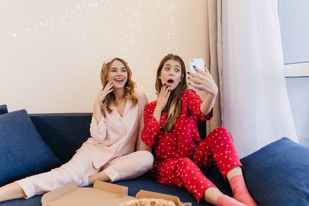 빨간 파자마와 양말 여동생과 함께 셀카를 만들고 놀라움을 표현하는 예쁜 소녀. 피자를 먹는 동안 재미 긍정적 인 여자 친구.