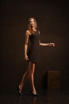 暗い壁に沿って歩くショートドレスでかわいい女の子