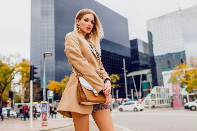 春のカジュアルな服装でかわいい女の子が屋外を歩いて、大きな近代的な都市で休日を楽しんでいます。ウールベージュのコートと剥奪されたブラウスを着ています。スタイリッシュなアクセサリー。