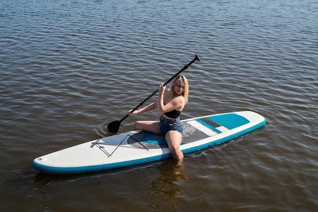 水の上のsupボードで休んでいる夏のかわいい女の子