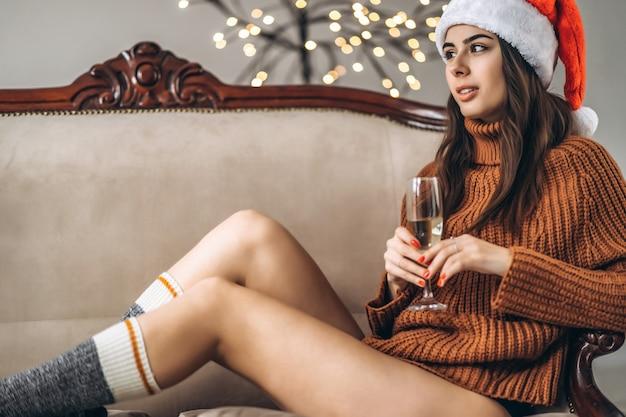 Красивая девушка в свитере и рождественской шляпе пьет шампанское