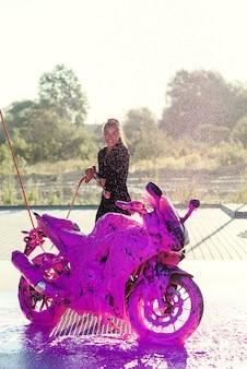 Симпатичная девушка в обтягивающем соблазнительном костюме моет мотоцикл и счастлива в автомойке самообслуживания.