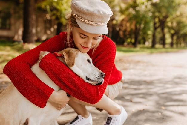 유행 모자와 흰색 운동화에 예쁜 여자가 그녀의 개를 부드럽게 안아줍니다. 공원에서 노는 그녀의 애완 동물과 함께 사랑스러운 금발.