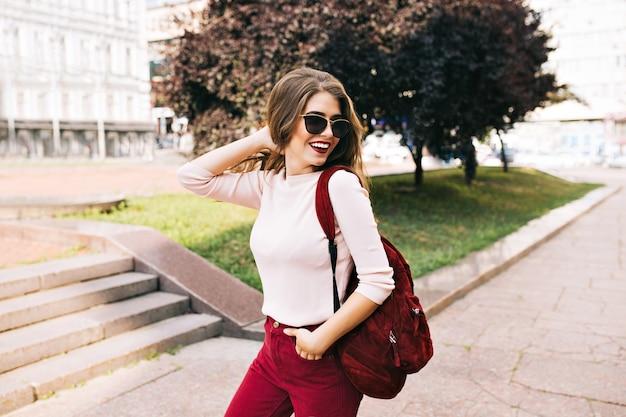 Красивая девушка в бордовых штанах в солнцезащитных очках идет по улице с сумкой. она улыбается и выглядит довольной.