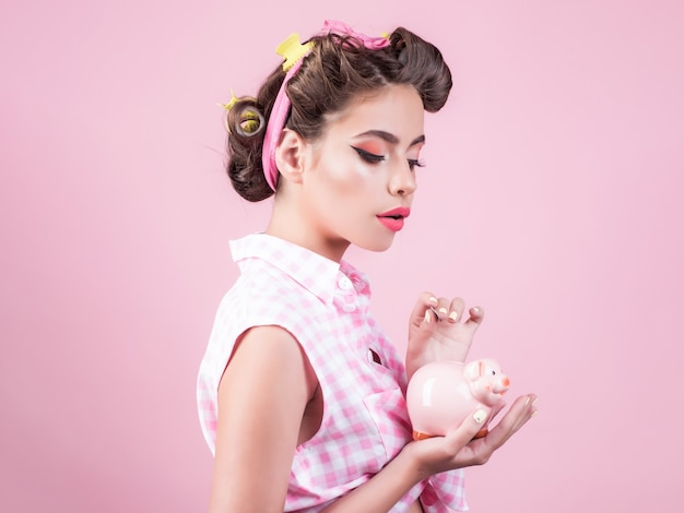 Красивая девушка в винтажном стиле с копилкой.