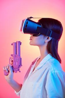 Красивая девушка в гарнитуре vr держит фиолетовый пластиковый пистолет во время стрельбы по виртуальной цели