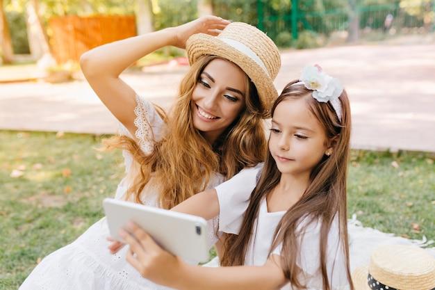 スマートフォンを持って、通りを歩いて笑っているお母さんと一緒に自分撮りをしている白いドレスを着たかわいい女の子。ブルネットの娘が写真を撮っている間、帽子をかぶってポーズをとってうれしい若い女性の屋外の肖像画。