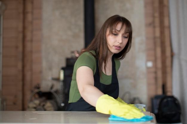 Красивая девушка в желтой перчатке с распылителем вытирает белую поверхность стола тканью
